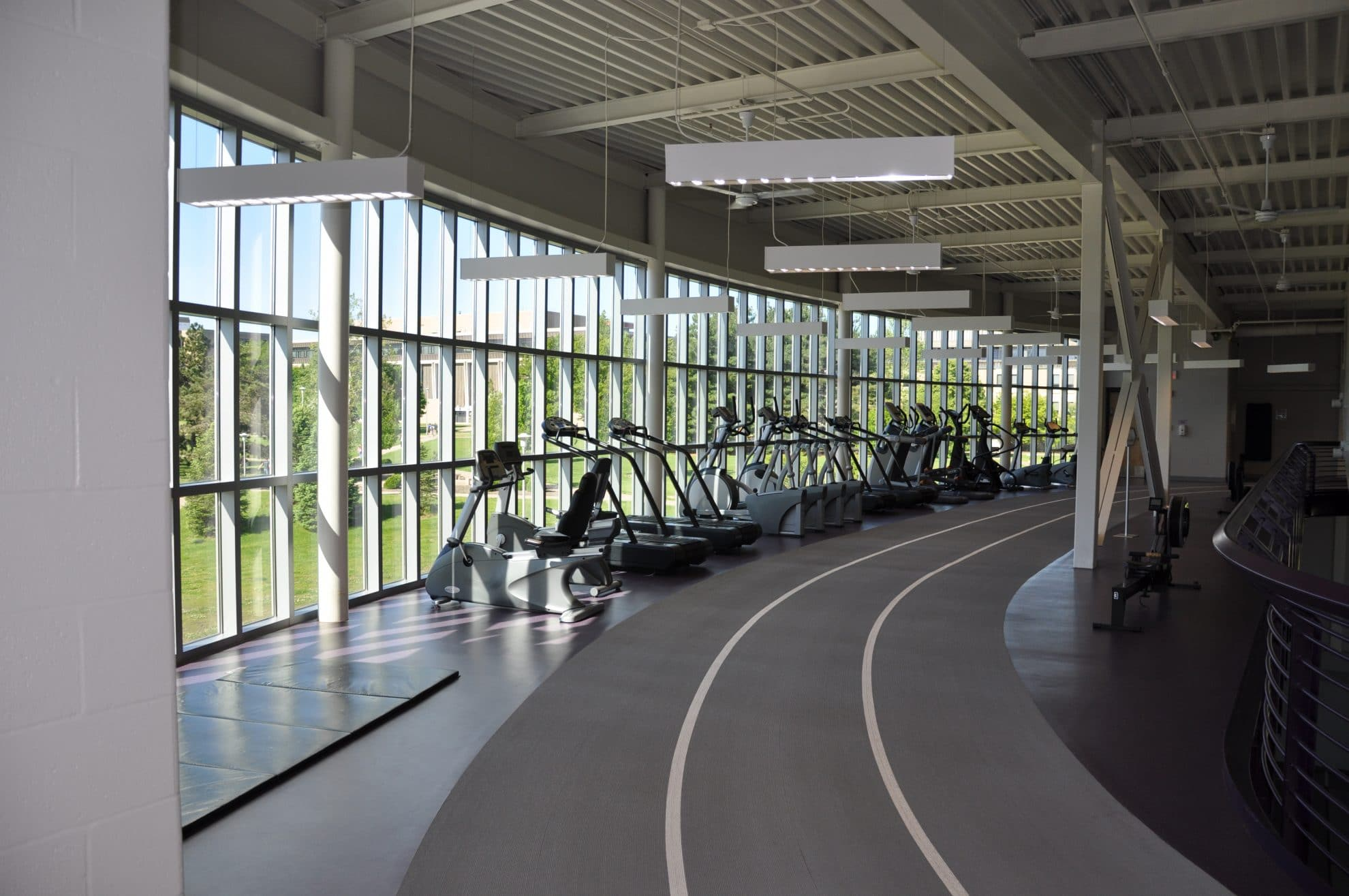 Workout equipment next to windows along track.
