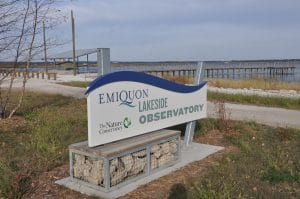 Outdoor sign by lake and walkway over water.