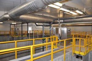 Indoor duct work and concrete walk ways with yellow railings.